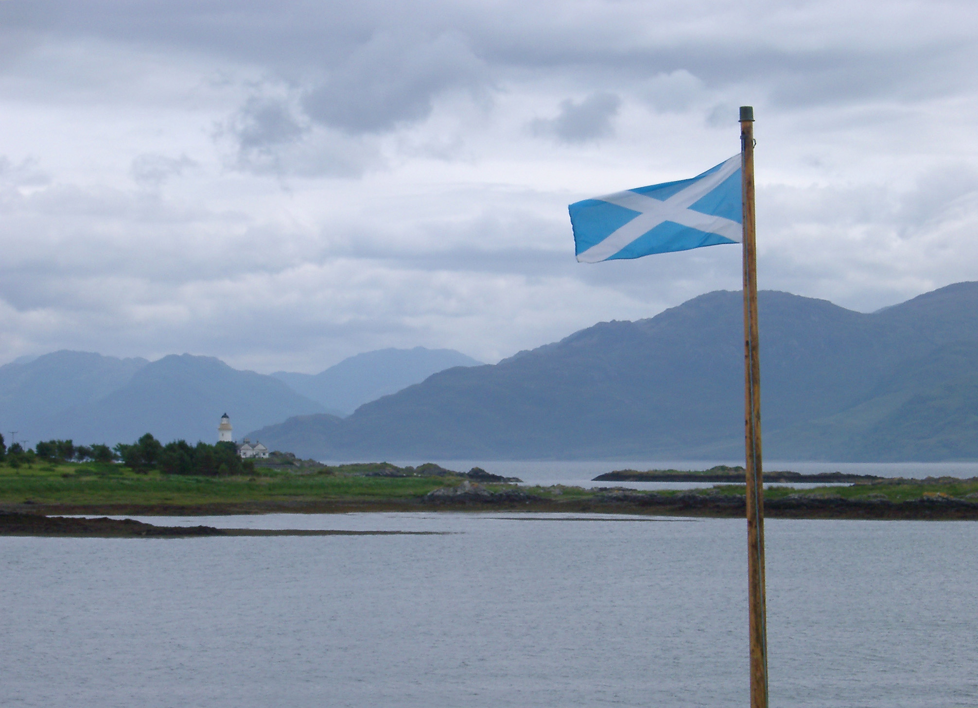 National flag of Scotland flying on a flagpole overlooking a placid loch on a cold cloudy day